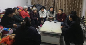 A still of a Chinese family sitting, crowded, in a living room. This is a still from The Choice.