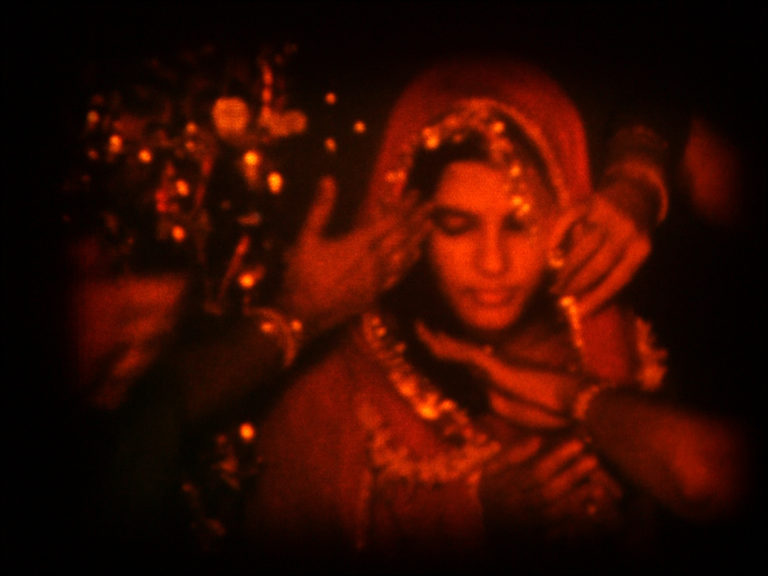 The image, a still from A Night of Knowing Nothing, is in a deep red hue. An Indian woman is dressed in clothing seemingly being prepared for a special occasion..