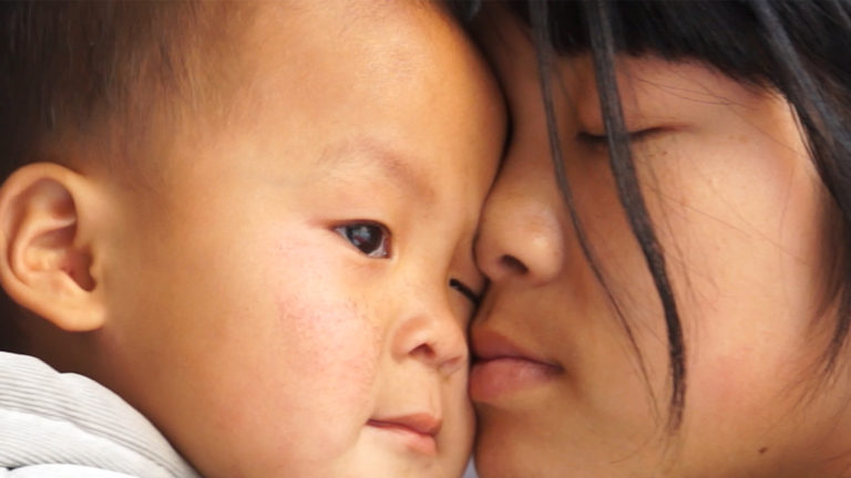 In a still from All About My Sisters, a Chinese woman holds a baby close to her face with her eyes closed. The image is a close-up of the two of them.