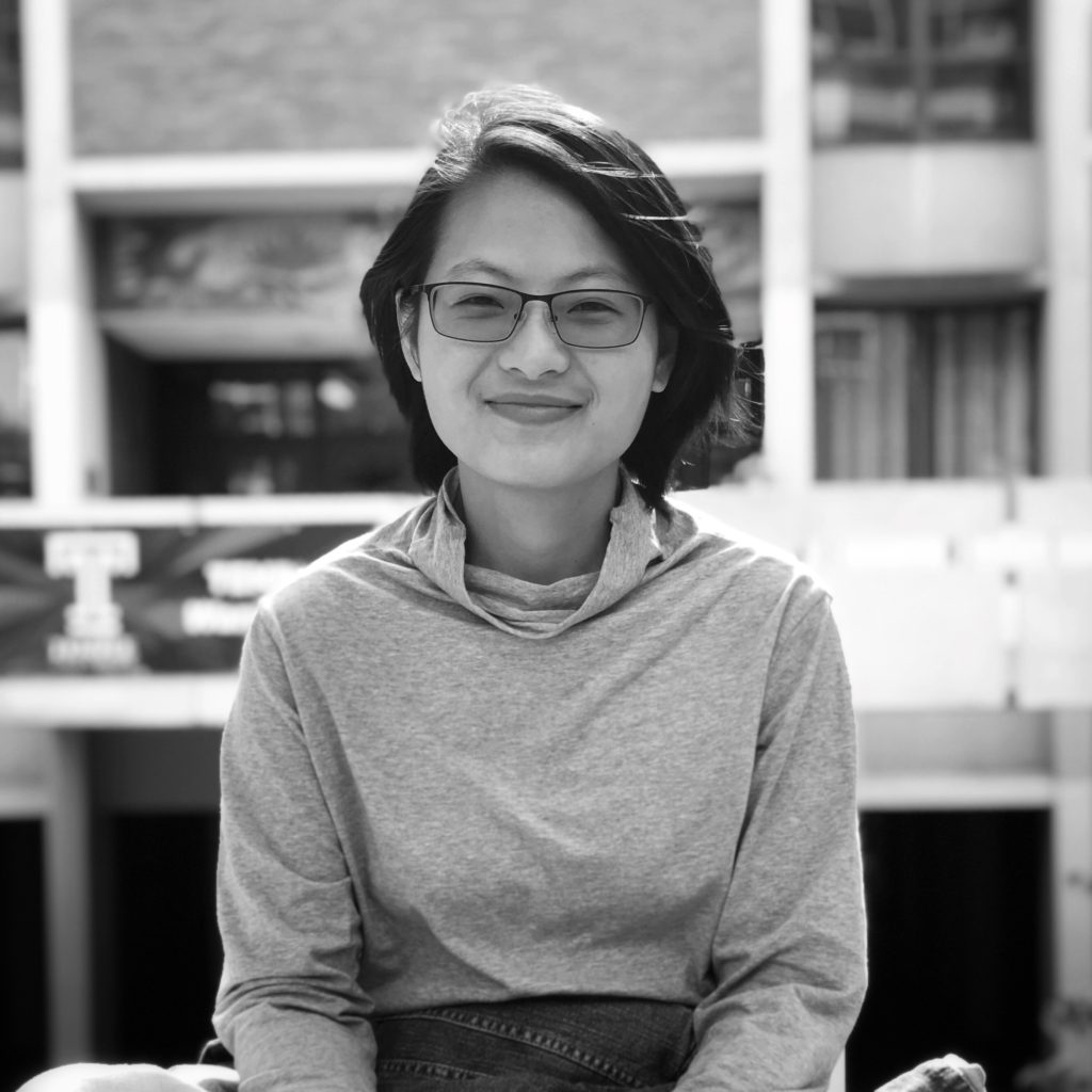 The image is a black and white portrait of All About My Sisters filmmaker, Qiong Wang. She is a Chinese woman with dark hair and glasses, and she is smiling directly at the camera.