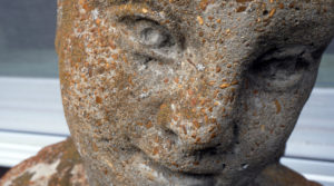 in a still from Her Socialist Smile, the image is a close-up shot of a stone statue of a woman. The statue is covered in browns and greens.