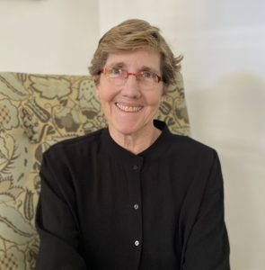 The image is a portrait of LEF Foundation Executive Director, Lyda Kuth. She is a white woman with short blond hair, and she is wearing a black shirt and glasses. She is sitting in a chair with a distinct green pattern.