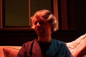 The image is a portrait of filmmaker Jordan Lord. Lord, a white person with blonde hair, is sitting on what looks to be a couch. They are being illuminated by orange and red light.