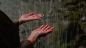 Two hands extended out to caress the rain: a still from maɬni – towards the ocean, towards the shore.