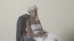 In a still from Prism, a Black woman is posing in front of a background. She is wearing a white dress and white head wrap. The chair she is sitting on is covered in a gray cloth. She is posed in a way reminiscent of the paintings by artist Johannes Vermeer.