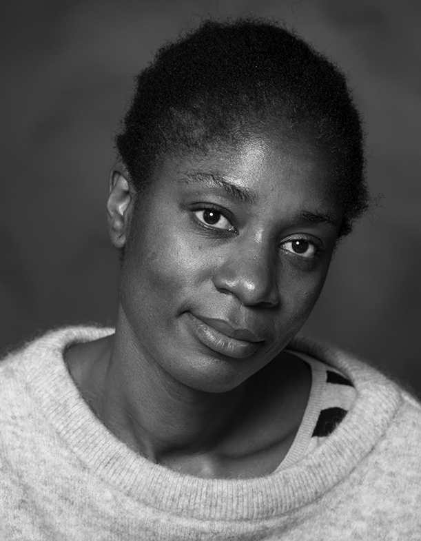 The image is a black and white portrait of director, Rosine Mbakam. She is a Cameroonian woman with short black hair. She is wearing a light colored sweater and is looking towards the camera with her head titled.